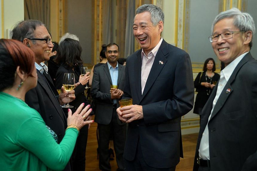 PM Lee Hsien Loong speaks to Ivy Goh Nair (in green) and her husband Chandran Nair (second from left), at a tea session in Shangri-La, Oct 27 2013. -- ST PHOTO: CAROLINE CHIA