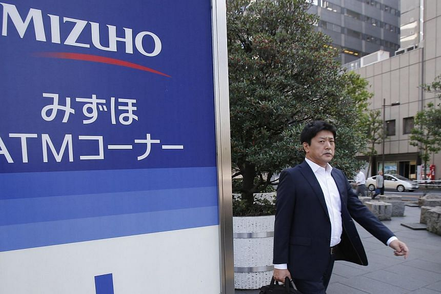 A man walks by a corporate sign of Mizuho Financial Group Inc in Tokyo on Monday, Oct 28, 2013. Mizuho Financial Group said on Monday that the chairman of its banking unit will resign, while its president will take a six-month pay suspension followin