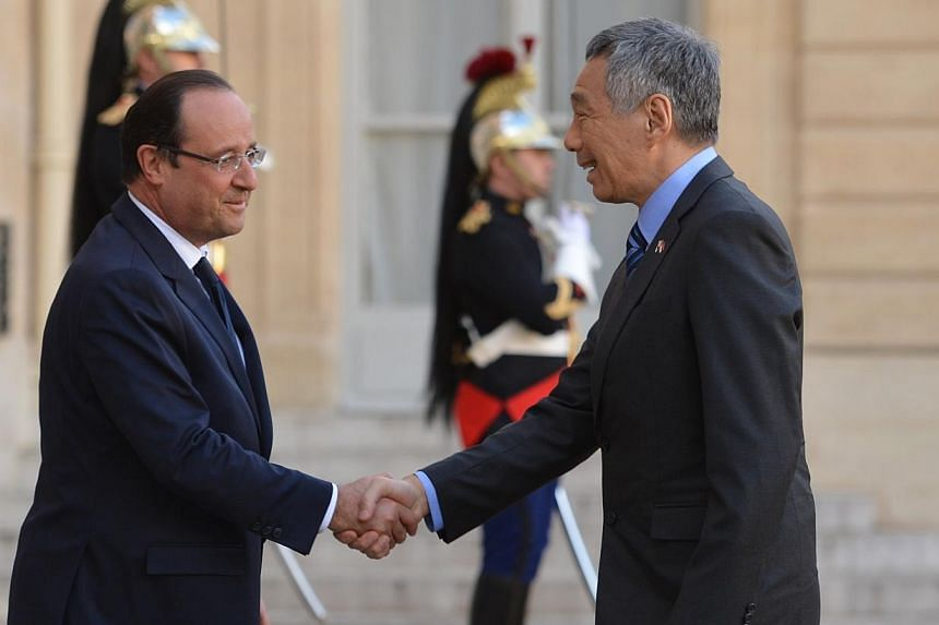 Prime Minister Lee Hsien Loong shakes hands with French PresidentFrancois Hollande.-- ST PHOTO:CAROLINE CHIA
