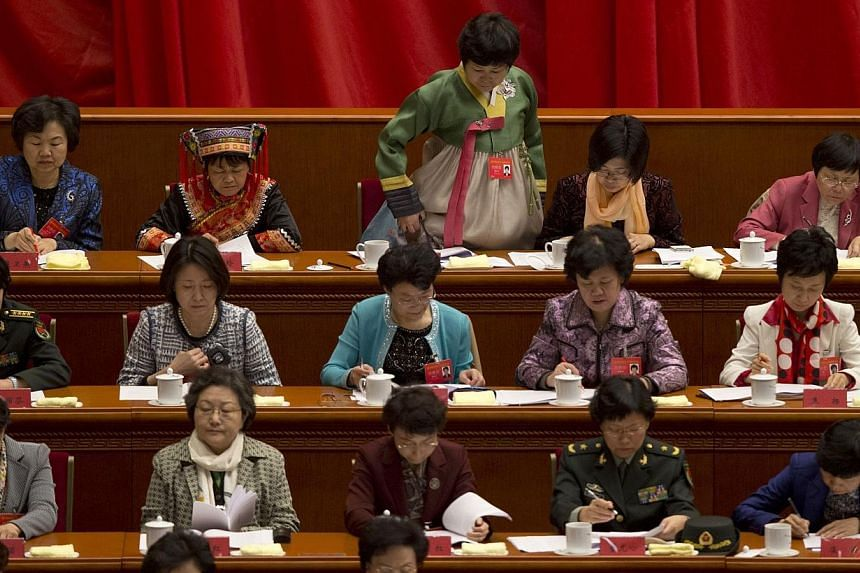 A delegate (back, centre), among others in their ethnic or professional suits, returns to her seat during the opening of the 11th National Women's Congress in Beijing's Great Hall of the People on Monday, Oct 28, 2013. See more pictures from around t