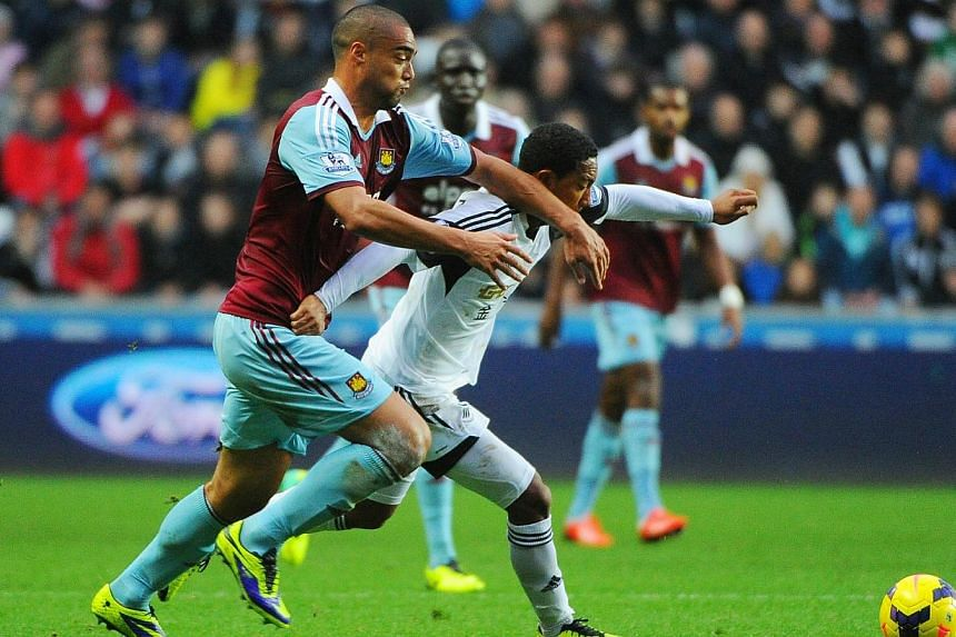 Swansea's Jonathan de Guzman, right, tussles with West Ham United's Winstone Reed, left, during the English Premier League soccer match at the Liberty Stadium, Swansea, Wales, on Sunday Oct. 27, 2013. Swansea and West Ham shared the points in a goall