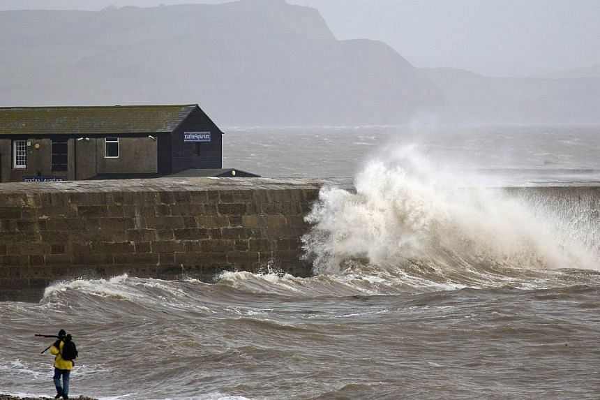 A photographer carrying a tripod walks along on the beach as waves crash into the sea wall in Lyme Regis, southern England on Oct 27, 2013 as high winds start ahead of an expected storm. -- PHOTO: AFP