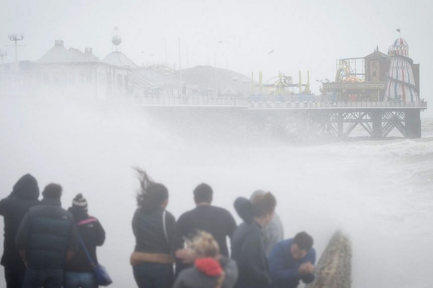 People watch as large waves crash against the walls of Brighton seafront, in southern England on Oct 27, 2013 as a predicted storm starts to build. -- PHOTO: AFP