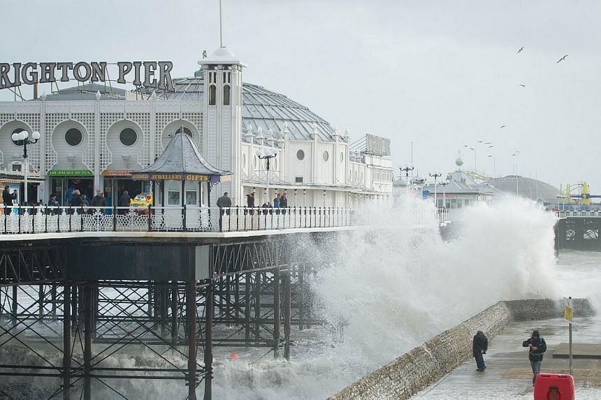 People look on as large waves crash against the walls of Brighton seafront, in southern England on Oct 27, 2013 as a predicted storm starts to build. -- PHOTO: AFP