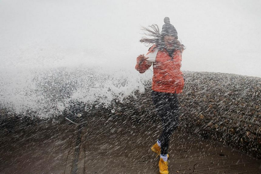 A woman is soaked as large waves crash against the walls of Brighton seafront, in southern England on Oct 27, 2013 as a predicted storm starts to build. -- PHOTO: AFP
