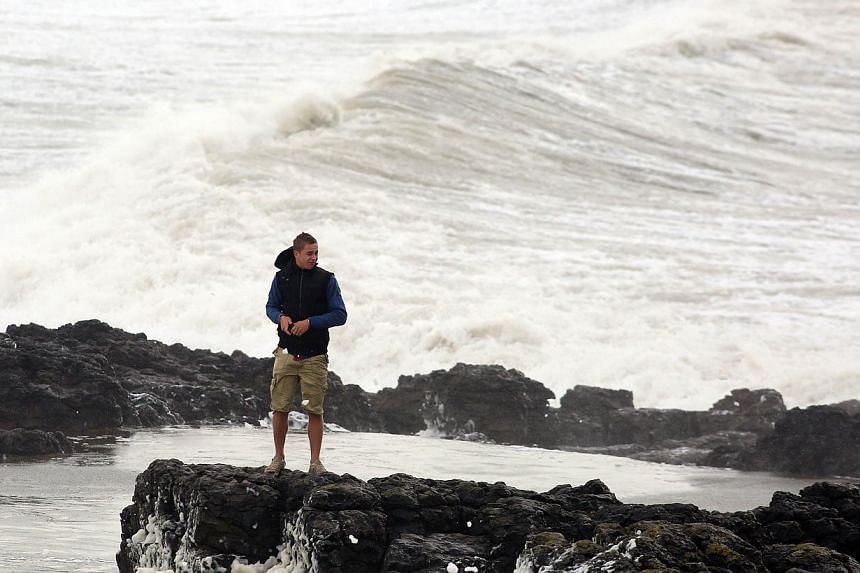 A man stands on a rocky outcrop as waves roll in to the beach in Porthcawl, south Wales on Oct 27, 2013 ahead of the arrival of a predicted storm. -- PHOTO: AFP