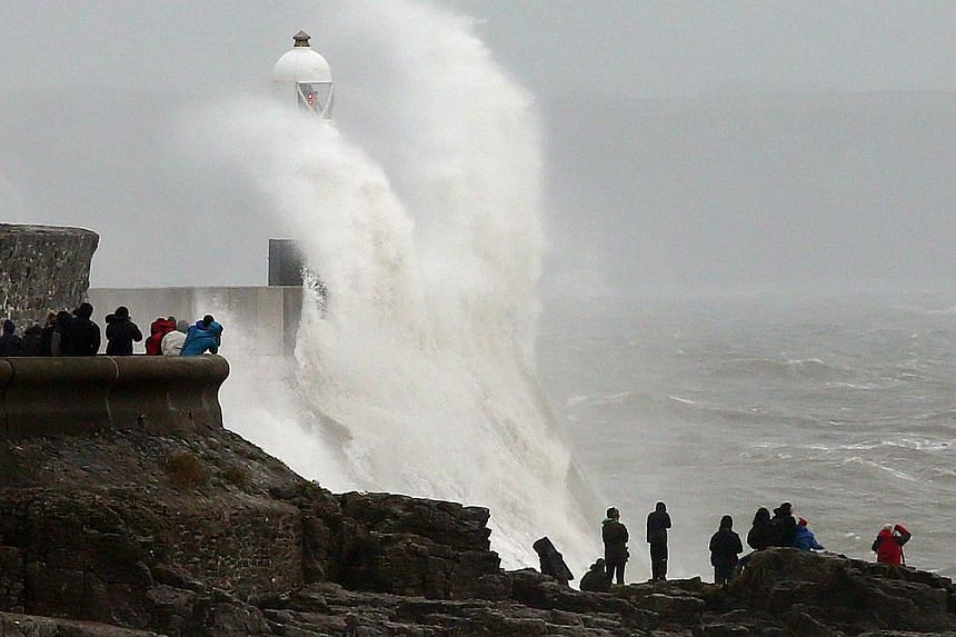 People watch as large waves break against barriers at the harbour in Porthcawl, south Wales on Oct 27, 2013 ahead of the arrival of a predicted storm. -- PHOTO: AFP