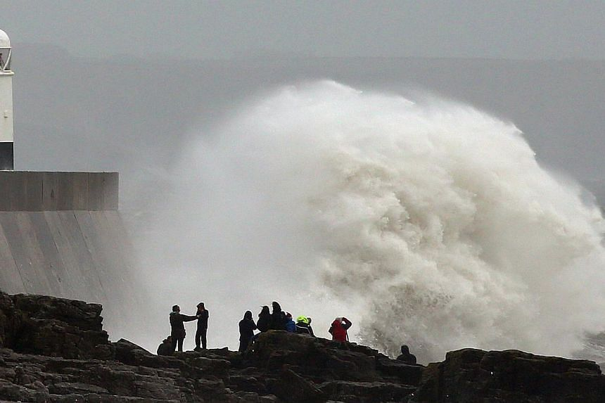People stand on the rocks as large waves break against barriers at the harbour in Porthcawl, south Wales on Oct 27, 2013 as a predicted storm starts to build. -- PHOTO: AFP