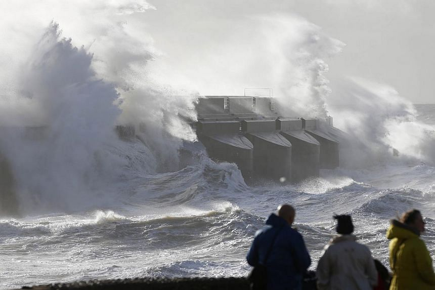 People watch the waves batter into the sea wall of a marina in Brighton, south England, Monday, Oct 28, 2013. A major storm with hurricane force winds is lashing much of Britain, causing flooding and travel delays including the cancellation of roughl