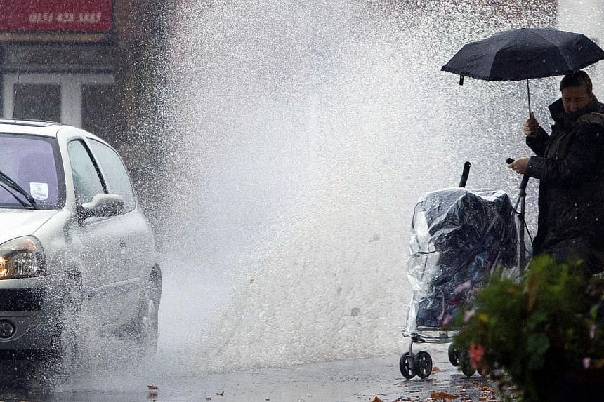 A lady with a child in a pram turns from the oncoming deluge from a passing car in Liverpool, England, after heavy rain fell over the country Monday Oct 28, 2013. -- PHOTO : AFP