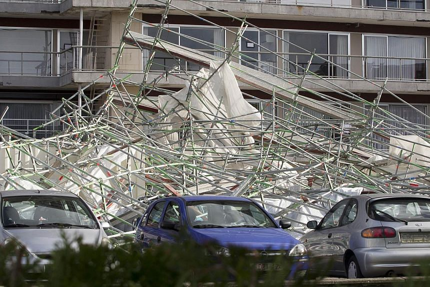 This picture taken on Oct 28, 2013 shows the debris on a parking lot next to an apartment building where a 13-floor high scaffolding came down due to the heavy winds in Merksem, Antwerpen. Nearly 300,000 homes were left without power in Britain and F