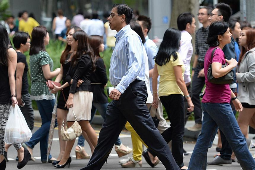 "Office workers and pedestrians crossing the road at Raffles Place. Singapore's economy is gradually regaining its upward momentum as the developed nations recover, prompting the central bank to tip ""modest growth"" for the local economy this year"
