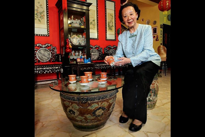 Madam Hoo Miew Oon, great-granddaughter of Hoo Ah Kay, better known as Whampoa, with some of the pots she has donated to the heritage museum. -- ST PHOTO: LAU FOOK KONG