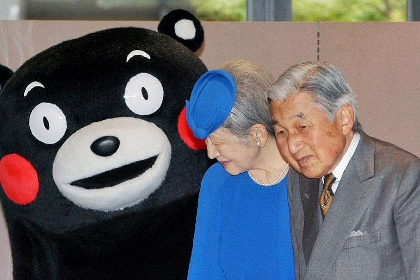 In this picture taken on Monday, Oct 28, 2013, (from right) Japanese Emperor Akihito and Empress Michiko stand next to Kumamon, Kumamoto prefecture's black bear mascot, as they visit the Kumamoto prefectural office in Kumamoto.He is instantly r