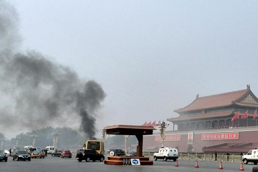 Vehicles travel along Chang'an Avenue as smoke rises in front of a portrait of late Chinese chairman Mao Zedong at Tiananmen Square in Beijing on Monday, Oct 28, 2013. The Chinese government suspects that Monday's incident in which a vehicle plo