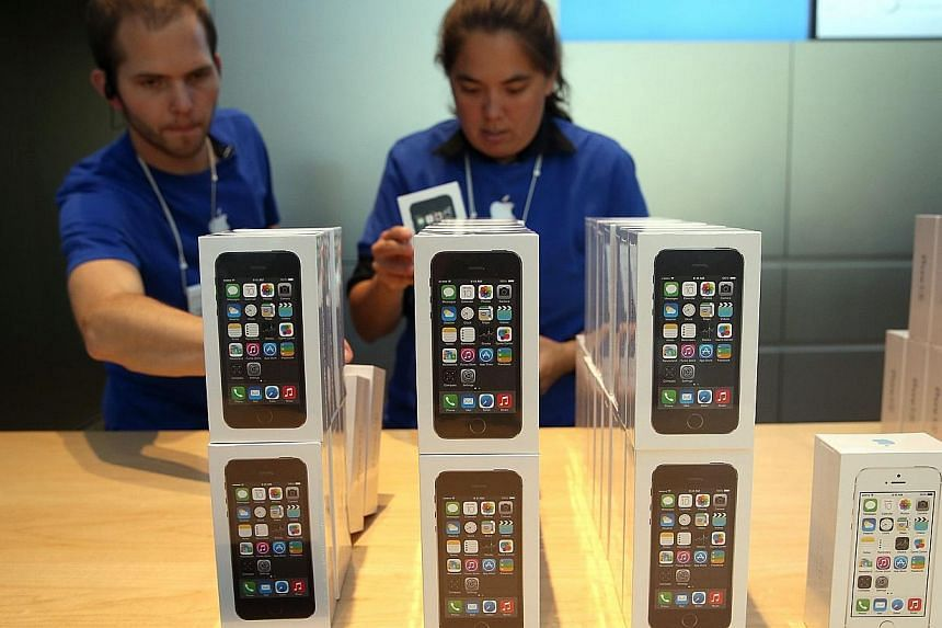 Apple Store employees stack boxes of the new Apple iPhone 5S on Sept 20, 2013 in Palo Alto, California. -- FILE PHOTO: AP