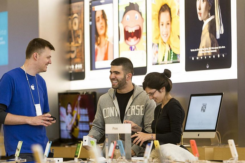 Customers buy the latest versions of the iPhone 5C and 5S at the Apple store at the Americana at Brand mall in Glendale, California, Friday, Sept 20, 2013. -- FILE PHOTO: AP