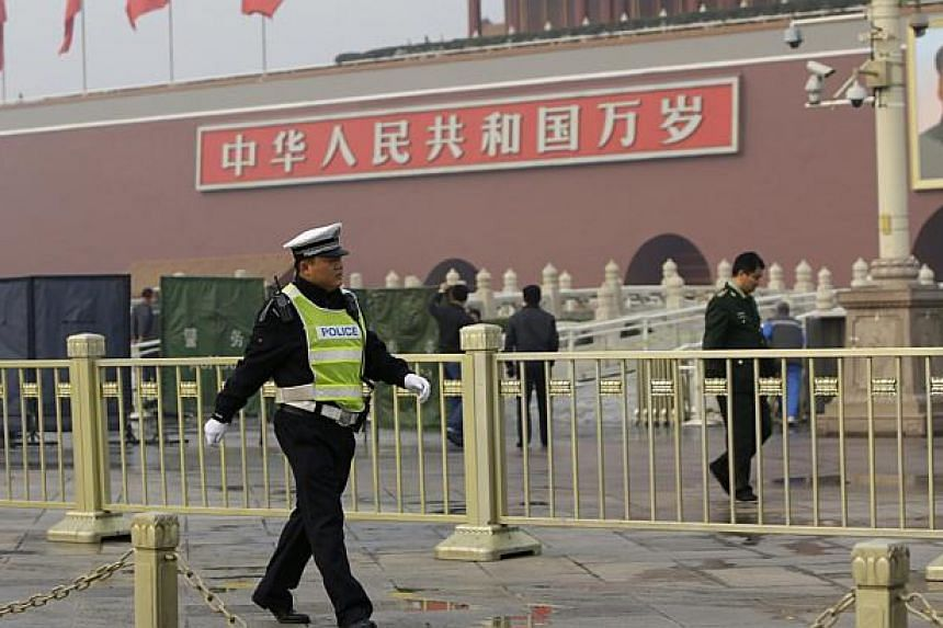 A policeman walks past in front of the giant portrait of the late Chinese Chairman Mao Zedong as other policemen clean up after a car accident at the Tiananmen Square in Beijing, Oct 28, 2013. -- PHOTO: REUTERS