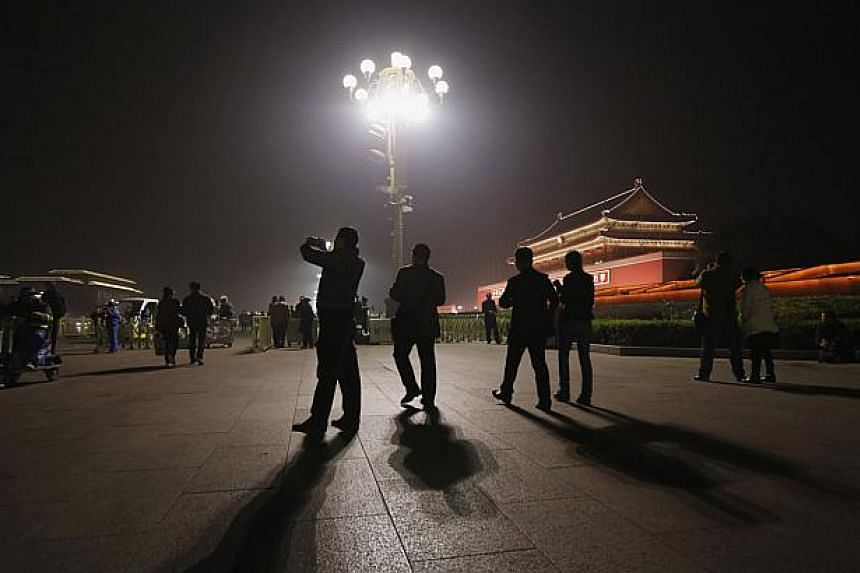 Visitors take picture near the main entrance of the Forbidden City in Beijing, on Oct 28, 2013. -- PHOTO: REUTERS