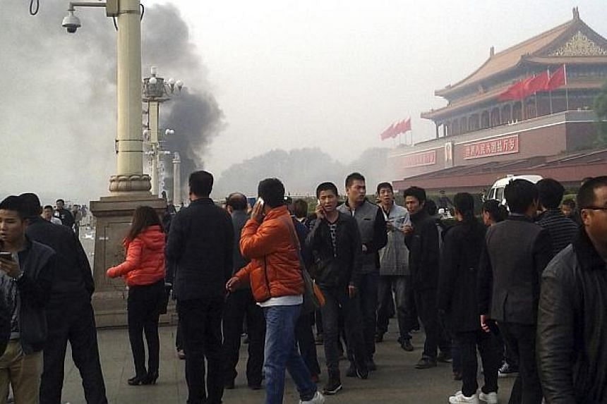 People walk along the sidewalk of Chang'an Avenue as smoke raises in front of the main entrance of the Forbidden City at Tiananmen Square in Beijing on Oct 28, 2013.. -- PHOTO: REUTERS