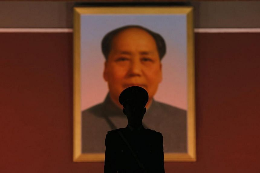A paramilitary policeman stands guard in front of the giant portrait of late Chinese Chairman Mao Zedong at the main entrance of the Forbidden City in Beijing, on Oct 28, 2013. -- PHOTO: REUTERS