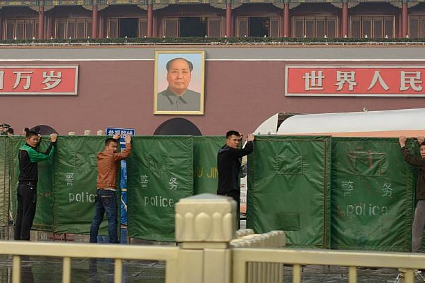 Plainclothes police hold barriers to shield the scene of a car crash in front of the iconic portrait of Mao Zedong at Tiananmen Gate in Beijing on Oct 28, 2013. -- PHOTO: AFP