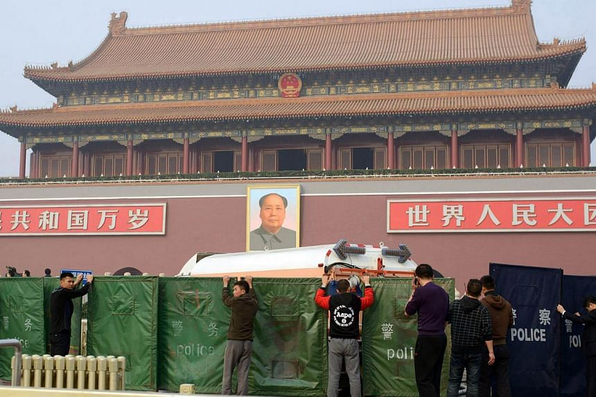 Workers stand before a police barrier outside Tiananmen Gate in Beijing on Oct 28, 2013 after a vehicle crashed near the area. -- PHOTO: AFP