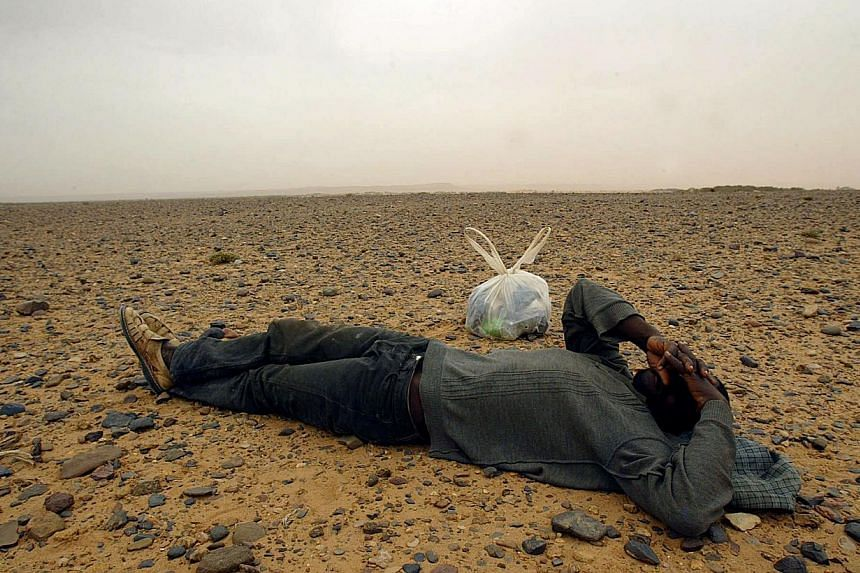 This picture taken on Oct 8, 2005, shows a would-be immigrant resting in the middle of the Sahara Desert, near the border with Algeria. Dozens of migrants from Niger heading for Algeria died of thirst in the Sahara desert after their vehicle broke do