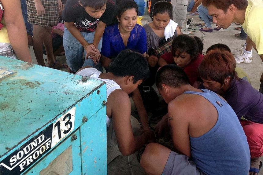 Residents of Sagbayan Municipality charging their mobile phones with a generator. The powerful 7.2 magnitude earthquake on Oct 15 knowcked down power lines. -- PHOTO: OCHA/ PRERNA SURI
