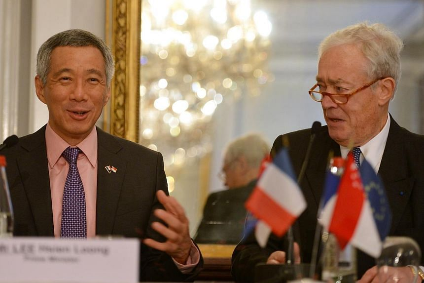 Prime Minister Lee Hsien Loong (left) reacts to a remark made by Mr Jean Burelle, chairman of Medef International. -- ST PHOTO: CAROLINE CHIA