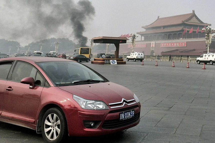 Vehicles travel along Chang'an Avenue as smoke raises in front of a portrait of late Chinese Chairman Mao Zedong at Tiananmen Square in Beijing, on Oct 28, 2013. A deadly car crash in Beijing's central Tiananmen Square received muted coverage in Chin