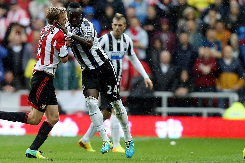 Newcastle United's captain Cheick Tiote, right, vies for the ball with Sunderland's Seb Larsson, left, during their English Premier League soccer match at the Stadium of Light, Sunderland, England, on Sunday, Oct 27, 2013.Newcastle's Ivory Coas