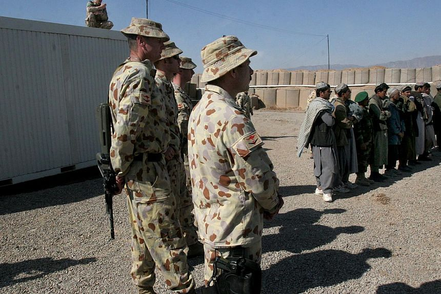 Australian soldiers, part of the International Security Assistance Force (ISAF), stand near local Afghans at a ceremony to open a Trade Training School, funded by Australian forces at the Tarin Kowt military base in Uruzgan province, south of Kabul,