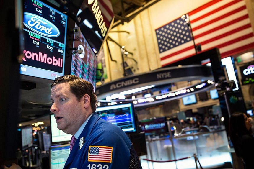 A trader works on the floor of the New York Stock Exchange on Oct 23, 2013 in New York City.The Dow and S&P 500 ended at record highs on Tuesday after economic data supported views that the Federal Reserve would keep its stimulus intact for