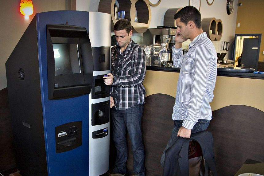 Vancouver Bitcoiniacs Trading Company co-founders Mitchell Demeter (right) and Jackson Hudson arrange, according to them, the first bitcoin ATM machine in a Waves Coffee House in Vancouver, British Columbia on Oct 28, 2013.  -- PHOTO: REUTERS&nb
