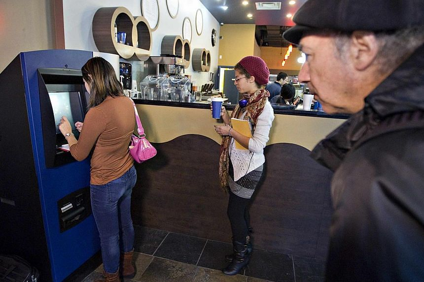 Customers line-up to use the world's first ever permanent bitcoin ATM unveiled at a coffee shop in Vancouver, British Columbia on Oct 29, 2013. The kiosk, built by Las Vegas RoboCoin and operated by local dealer Bitcoiniacs, will allow users to withd