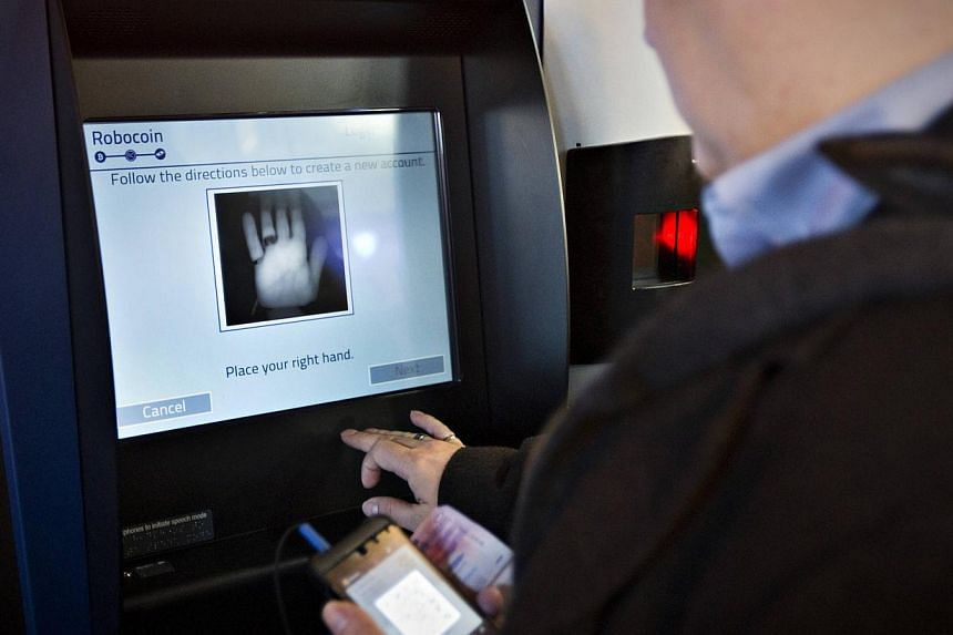 A customer registers his hand print before proceeding on the world's first ever permanent bitcoin ATM unveiled at a coffee shop in Vancouver, British Columbia on Oct 29, 2013. -- PHOTO: AFP