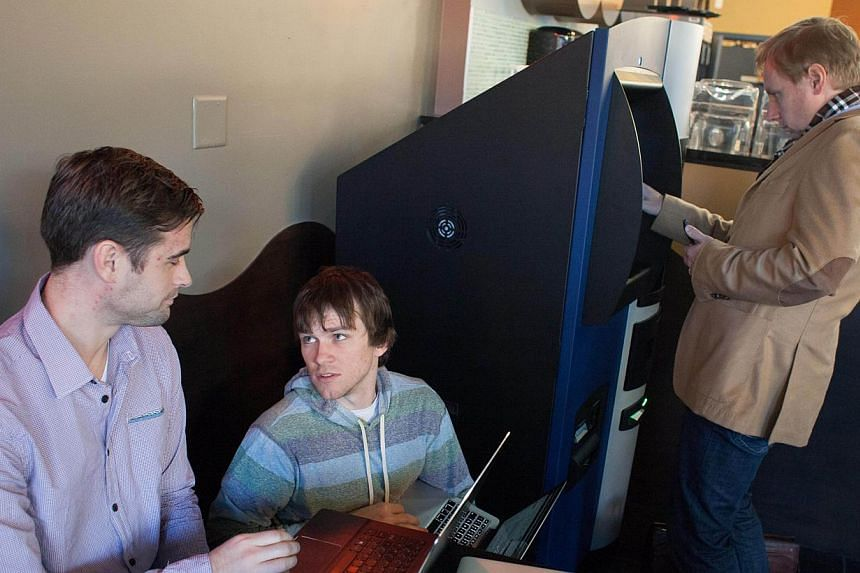 Mr Jackson Warren, left, of Bitcoiniacs, and John Russell, centre, of Robocoin, monitor transactions on the world's first bitcoin ATM, being used by Marc van der Chijs, right, at Waves Coffee House on Oct 29, 2013 in Vancouver, British Columbia, Cana