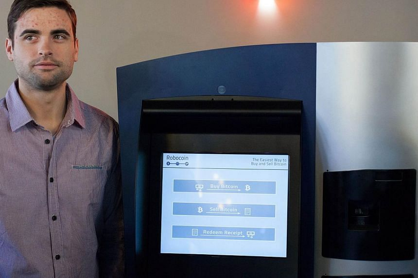 Mr Jackson Warren, co-founder of Bitcoiniacs, is pictured with the world's first bitcoin ATM at Waves Coffee House on Oct 29, 2013 in Vancouver, British Columbia, Canada.  -- PHOTO: AFP