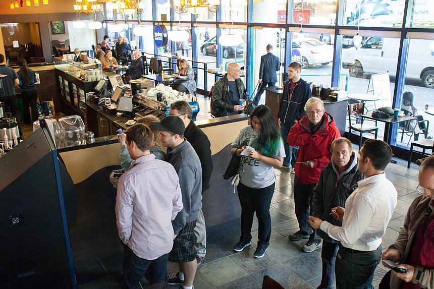 Users wait in line to use the world's first bitcoin ATM at Waves Coffee House on Oct 29, 2013 in Vancouver, British Columbia, Canada.  -- PHOTO: AFP