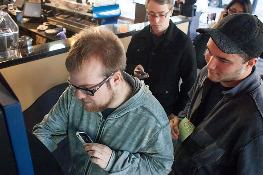 Mr Curtis Machek, left, uses the world's first bitcoin ATM at Waves Coffee House on Oct 29, 2013 in Vancouver, British Columbia, Canada.  -- PHOTO: AFP