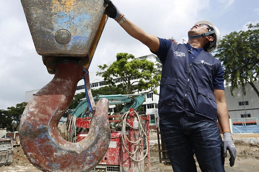 Deputy director Mohd Ismadi from MOM's Occupational Safety and Health Division checking the hook of a crane during an inspection at a MacPherson Road site on Monday. -- PHOTO: DESMOND LUI FOR THE STRAITS TIMES