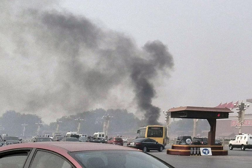 Vehicles travel along Chang'an Avenue as smoke rises in front of a portrait of late Chinese chairman Mao Zedong at Tiananmen Square in Beijing on Monday, Oct 28, 2013.Chinese police announced on Wednesday, Oct 30, 2013, they have captured five