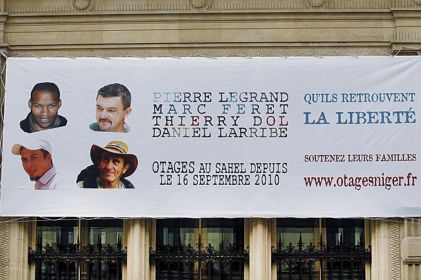 This Monday, Sept 16, 2013, file photo shows a banner with the portraits of the French hostages that were kidnapped in Niger three years ago, set up on the fourth district city hall in Paris, France. The four Frenchmen have been released after more t