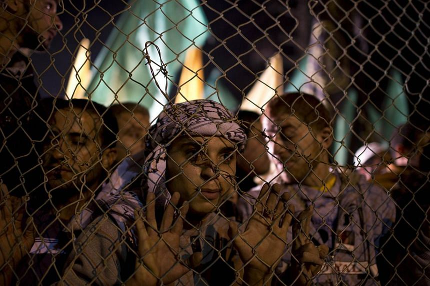 Palestinian prisoners' relatives wait behind a fence for their release at Erez point in the northern Gaza Strip on Oct 29, 2013. -- PHOTO: AFP
