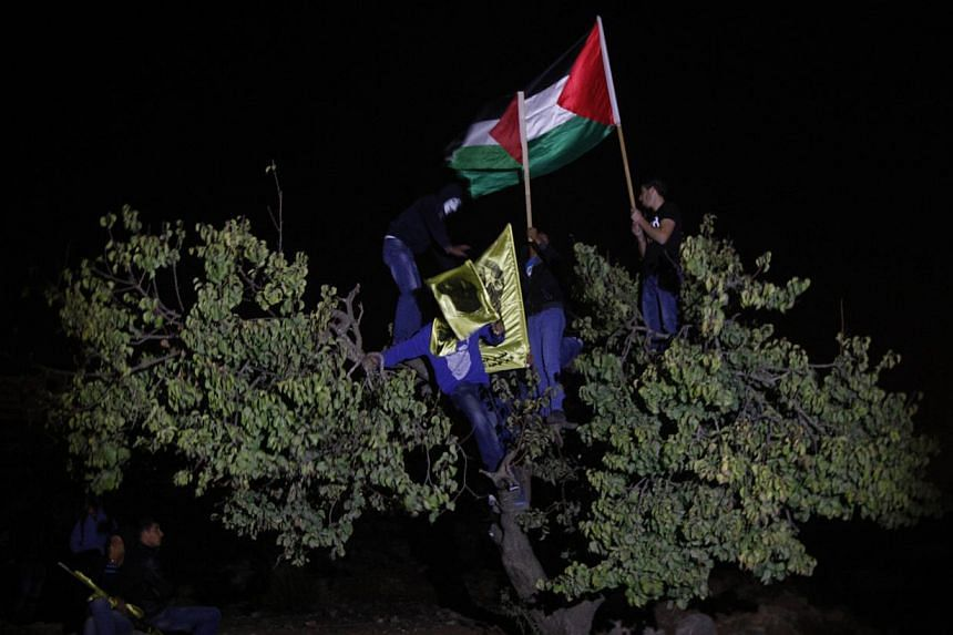 Palestinians hold up Palestinian flags to celebrate as they wait for the arrival of released prisoners outside Ofer prison near the West Bank town of Ramallah, early on Wednesday, Oct 30, 2013. -- PHOTO: AP