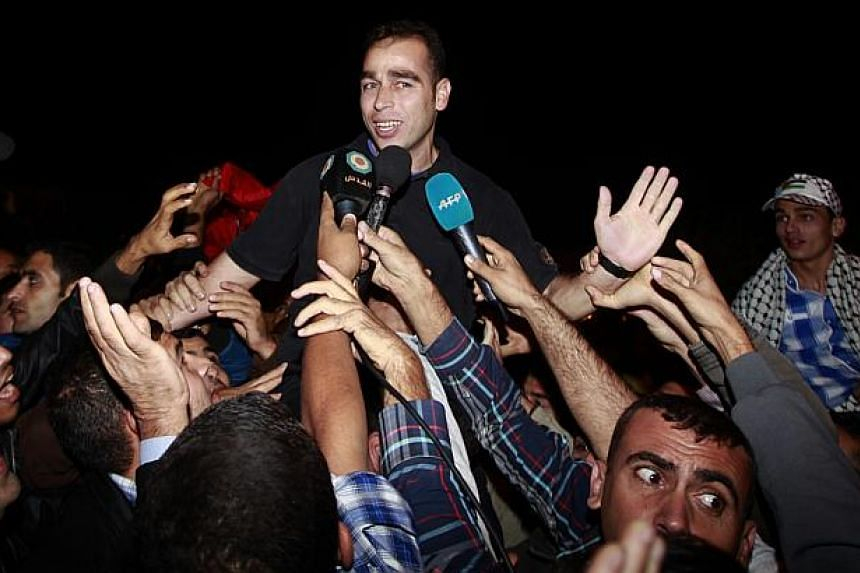 A released Palestinian prisoner is greeted by people upon his arrival at Erez crossing between Israel and northern Gaza Strip on Oct 30, 2013. -- PHOTO: REUTERS