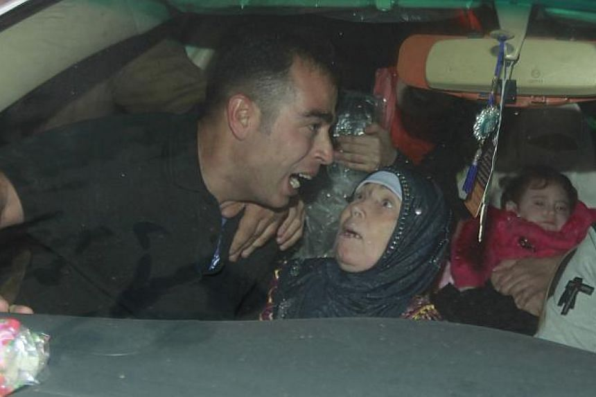 A released Palestinian prisoner (left) reacts as he sits next to his mother in a car upon his arrival at Erez crossing between Israel and northern Gaza Strip on Oct 30, 2013. -- PHOTO: REUTERS
