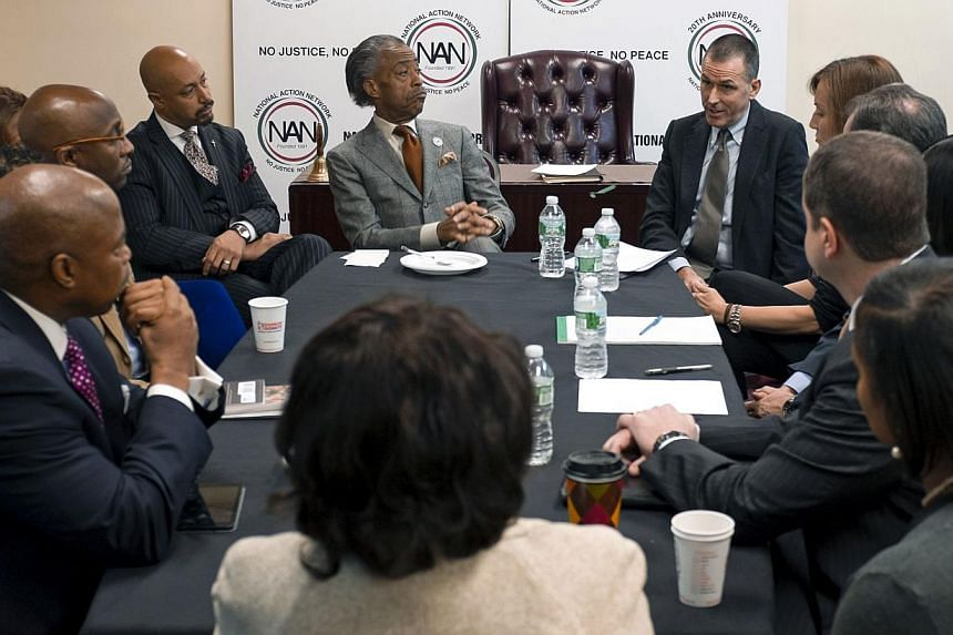 Reverend Al Sharpton (centre), listens as Barneys New York chief executive Mark Lee (right) speaks during a meeting at the National Action Headquarters in New York, on Oct 29, 2013. New York state's attorney general on Tuesday launched an investigati