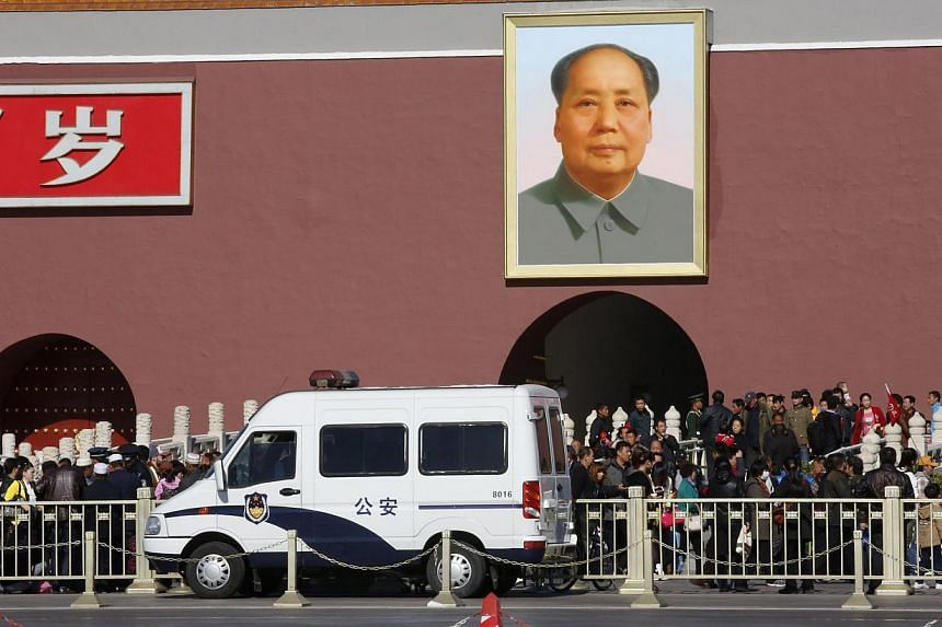 """A police car is parked in front of the giant portrait of late Chinese Chairman Mao Zedong at the main entrance of the Forbidden City in Beijing, on Oct 29, 2013. An overseas Uighur rights group fears a """"fierce state crackdown"""" by China on the largely"""